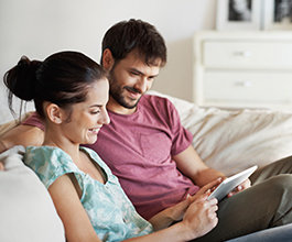 Image of couple on couch reading a tablet