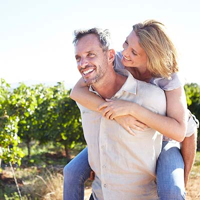 A man carrying a woman through vineyards