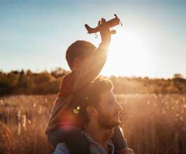 Boy holding toy plane on fathers shoulders